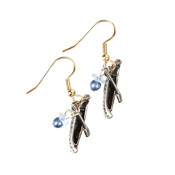 Two miniature canoe earrings with tiny paddles and shepherd hooks.