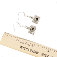 Two camera earrings next to a ruler, approximately 1.75 inches in length