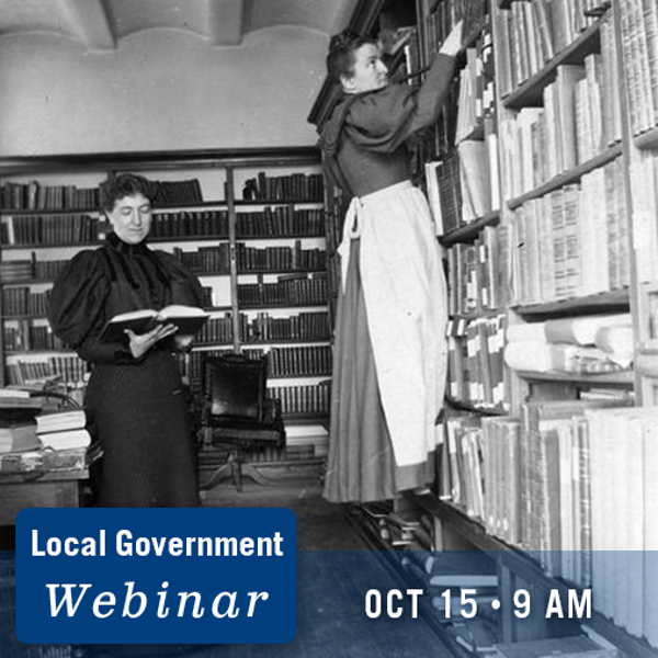 Two librarians wearing dresses shelving books. Local Government Webinar October 15, 2021. 9 a.m..
