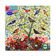 Front of puzzle box. 12 colorful songbirds are percehd in a tree with a flower garden below.